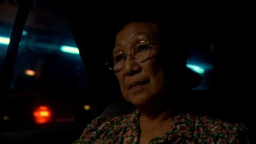 Mak Fong contemplates quietly in a scene from WOMAN ON FIRE LOOKS FOR WATER