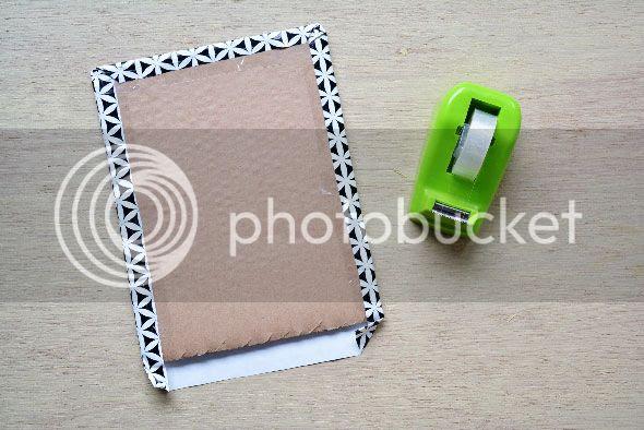 Plak het inpakpapier op het karton en vouw de randen om + bevestig ze met plakband.