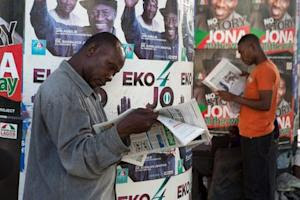 Men read newspapers in front of electoral campaign…
