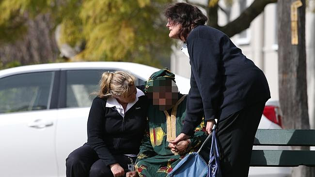 A visibly upset woman is comforted near the house in Wallsend. Picture: Liam Drive