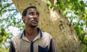 Getachew Merah, a 30-year-old migrant from Ethiopia, stands by a tree near Metema, on 4 June 2015.