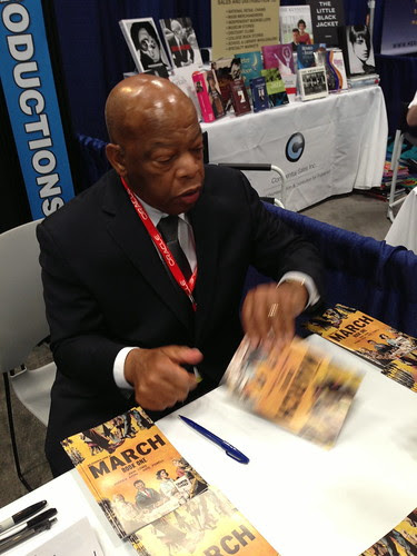 Hero Congressman John Lewis handing a signed book to a fan, BEA 2013