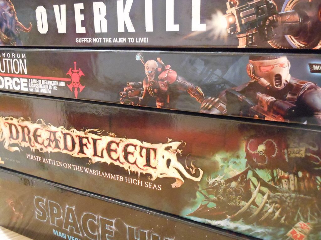 A stack of Games Workshop board games, including Deathwatch: Overkill, Assassinorum, Dreadfleet, and Space Hulk.