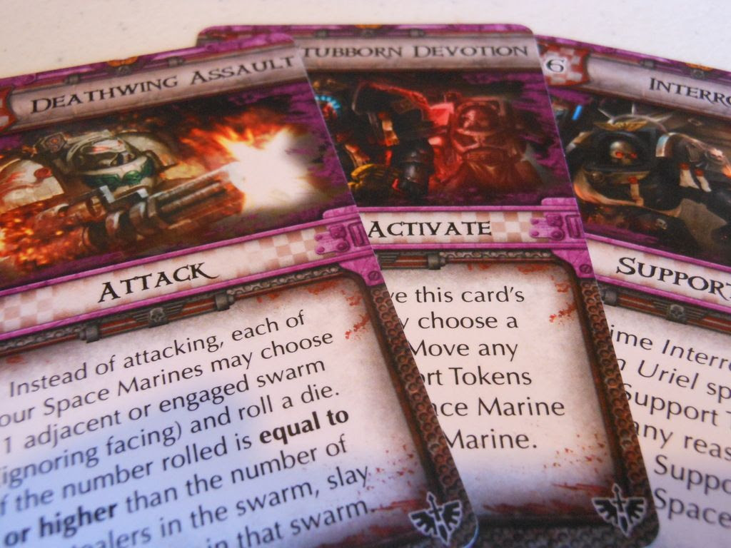 Close up view of Space Hulk: Death Angel - Deathwing action cards, showing details of the artwork depicting space marines in deadly combat with aliens.