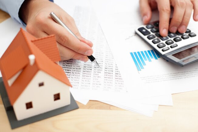 Closeup of a man calculating payments for a home.