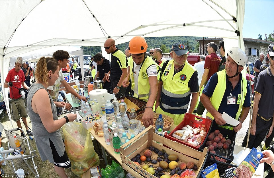 Rescue workers grab some food at the tent camp refectory  in Arquata del Tronto, Italy. Food has been donated by the Red Cross