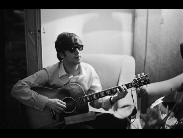 John Lennon (1940 ­ 1980) of the Beatles plays the guitar in a hotel room in Paris, 16th January 1964.