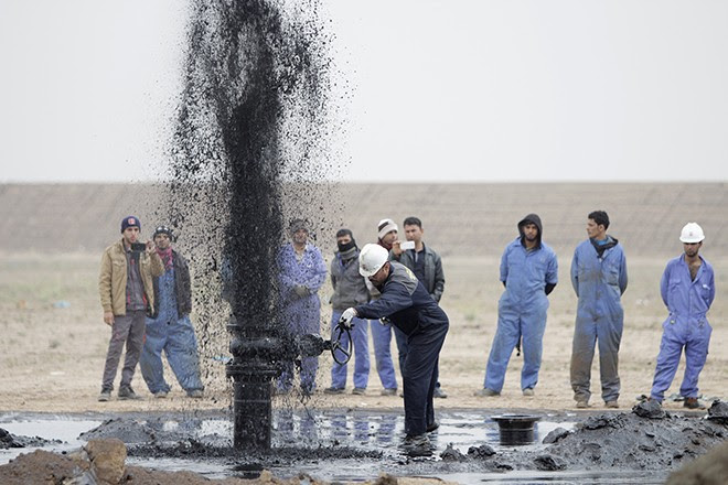 Iraqi workers stand near a pipeline as it ejects oil at Al Tuba oil field in Basra