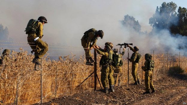 Israeli soldiers inspect a fire near Kfar Sold, north of Israel, caused by four missiles fired from the Syrian side of the Israeli-Syrian border hitting open areas in the Golan Heights and Galilee, causing the fire, on 20 August 2015.