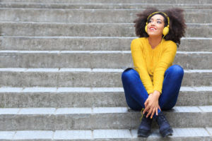 A person sitting on stone stairs, appearing happy as they listen to music from their bright yellow headphones.