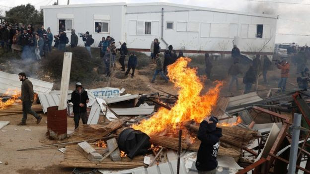 Protesters set furniture on fire during an operation to evacuate the unauthorised settlement outpost of Amona in the occupied West Bank (1 February 2017)