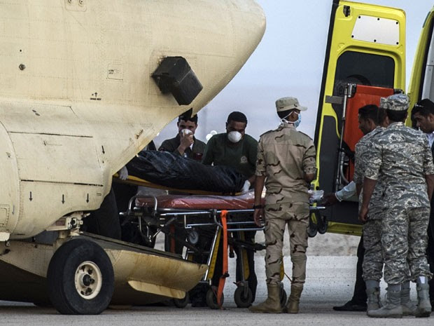 Paramédicos egípcios transportam corpos das vítimas da queda do avião russo em aeronave militar.   (Foto: AFP PHOTO / KHALED DESOUKI )