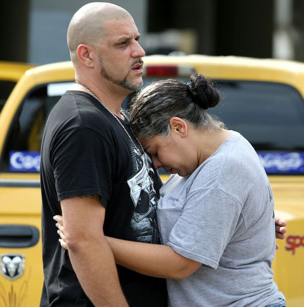 Ray Rivera, DJ at the Pulse nightclub, is consoled by a friend outside of the Orlando Police Department
