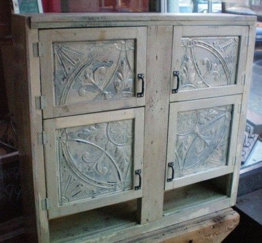 This cabinet gets a new life with sections of tiles cut to fit into the front door panels. The patina of the tin matches the age of the wood perfectly.