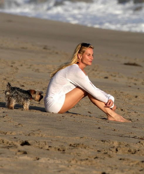 Actress Nicollette Sheridan wearing a short white dress and playing with her dog on the beach in Malibu.