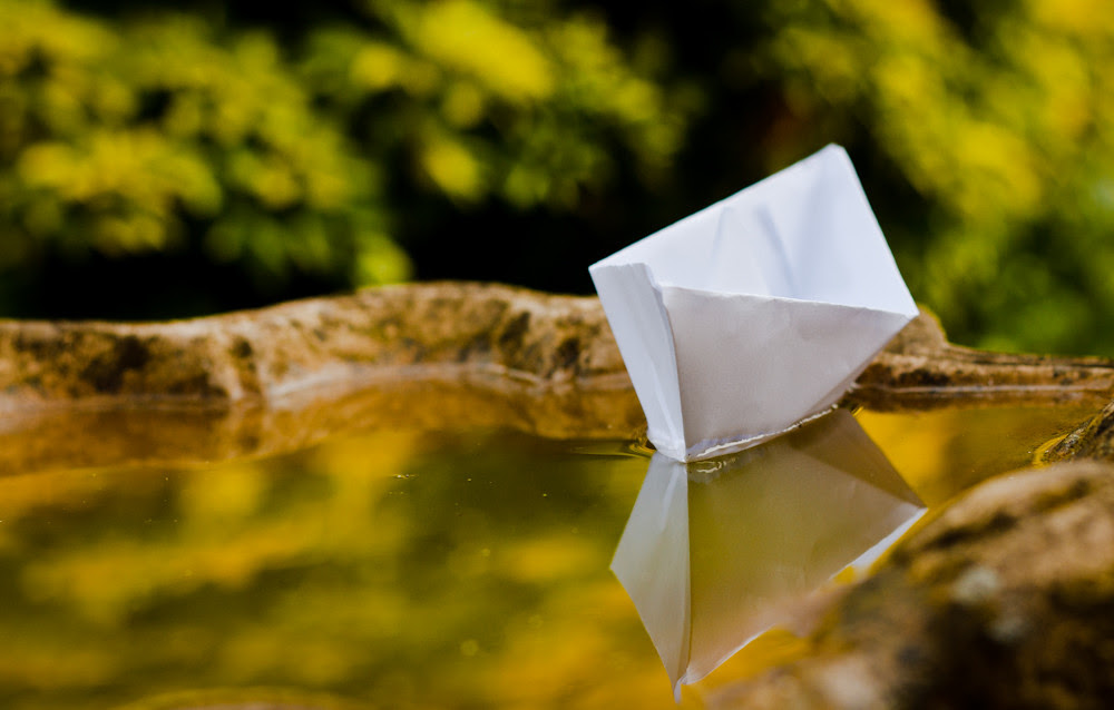 Paper boat in bird bath