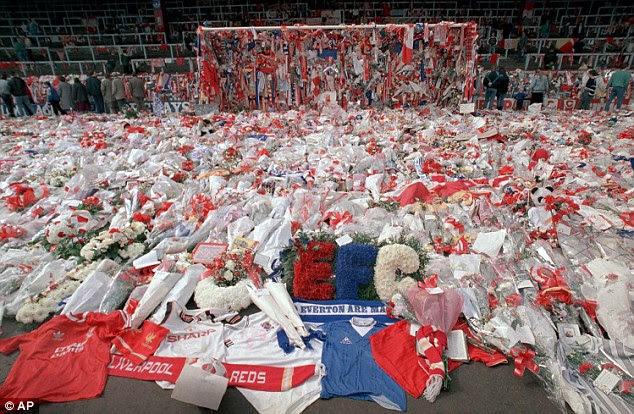 A shirt of local rivals Everton is among thousands of flower tributes laid at Anfield shortly after the disaster