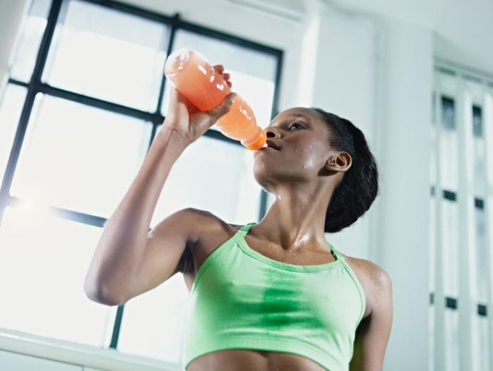 woman at gym drinking juice