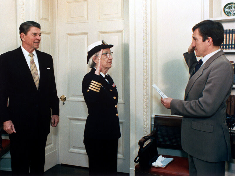 Secretary of the Navy John Lehman (right) promotes Grace Hopper to the rank of commodore in a ceremony at the White House with President Ronald Reagan.