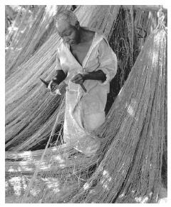 A Tanzanian fisherman mends his net in Nungwi, Zanzibar, Tanzania. Dried or fried fish is a staple food.