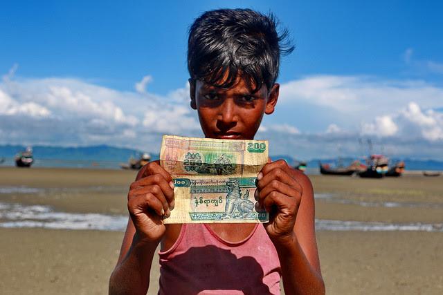 Twelve-year-old Rohingya boy Nur Mohammad holds up Myanmar currency in Shah Porir Dwip. Credit: Farid Ahmed/IPS