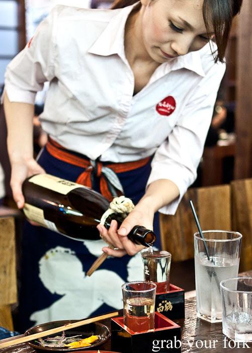 sake pouring at the table at yebisu izakaya, regent place sydney