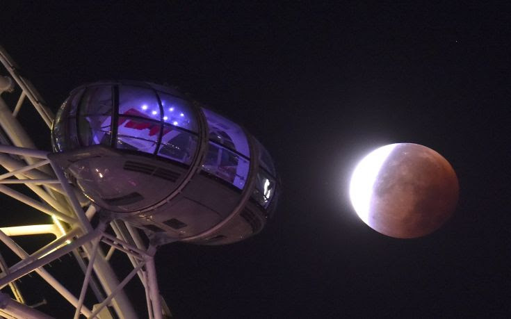 A supermoon is seen during a lunar eclipse behind pods of the London Eye wheel in London