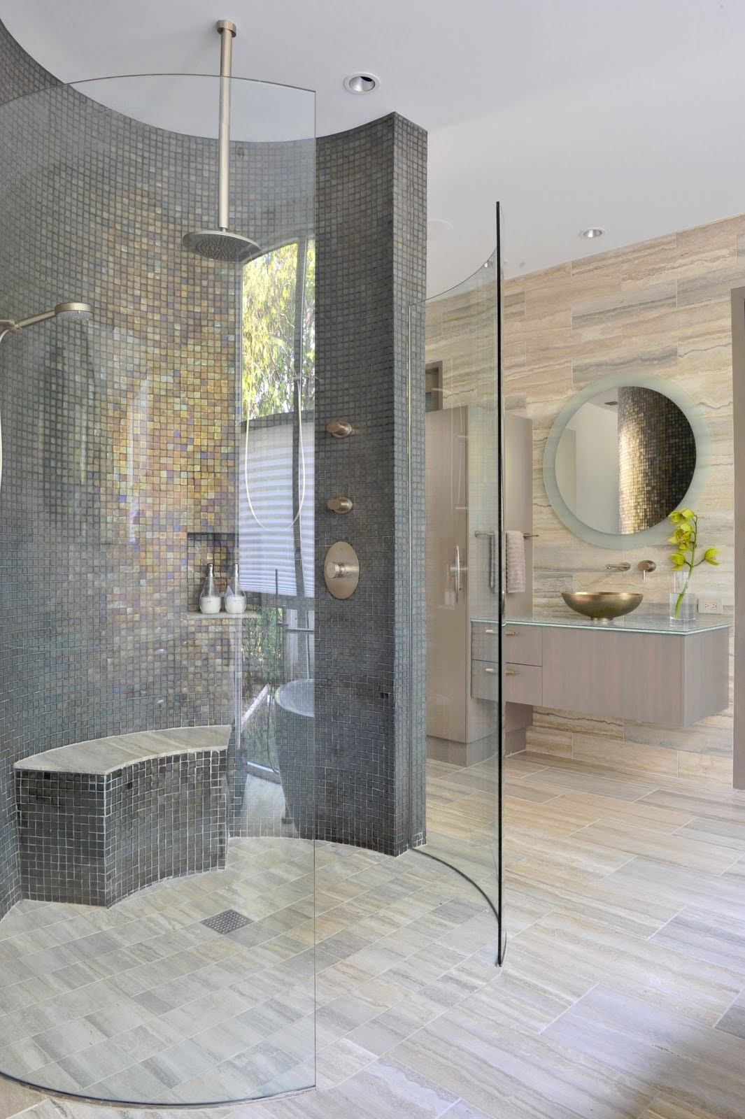 stunning and luxurious modern bathroom design idea with round glass shower design with bench and small tile mosaic pattern and lighting and round wall mirror