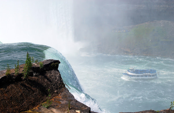 The Niagara River flows over the Falls with the Maid of the Mist in the mists below.