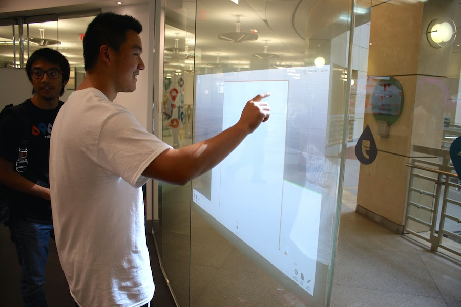 BYA member Robert Shi draws on an interactive wall.
