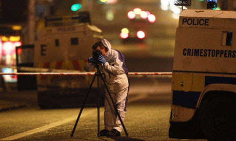 Forenics officer photographs a burnt police patrol car