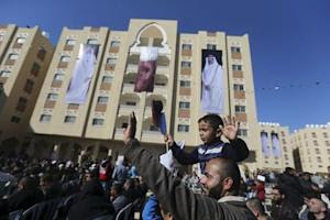 "Posters depicting Qatar's former Emir Sheikh Hamad bin Khalifa al-Thani and Emir of Qatar Tamim bin Hamad al-Thani are seen on a building as Palestinian man holding his son waves during the opening ceremony of ""Hamad City"", in the southern Gaza Strip"