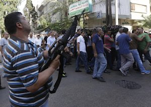 A Lebanese Shiite gunman fires by his rifle as mourners,…