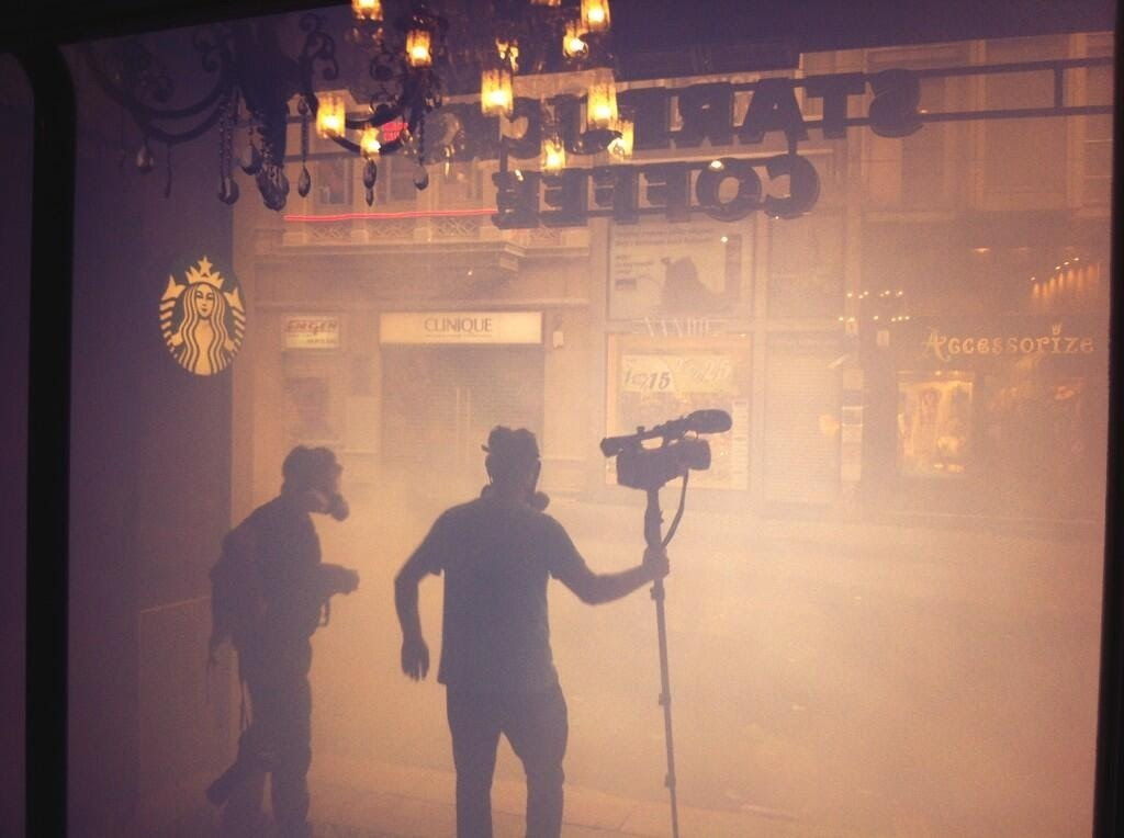 Tear gas along Istiklal Ave. People take refuge inside a Starbucks.