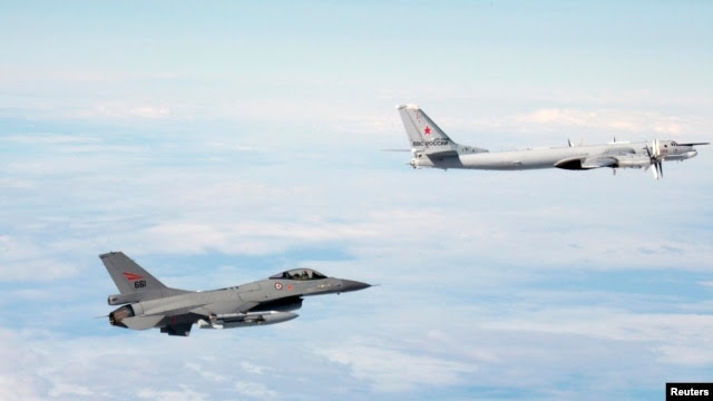 A Norwegian F-16 jet fighter (left) tracks a Russian Tupolev Tu-95 strategic bomber earlier this year. In 2014, there was a marked increase in the number of times NATO aircraft intercepted Russian planes probing alliance defenses.