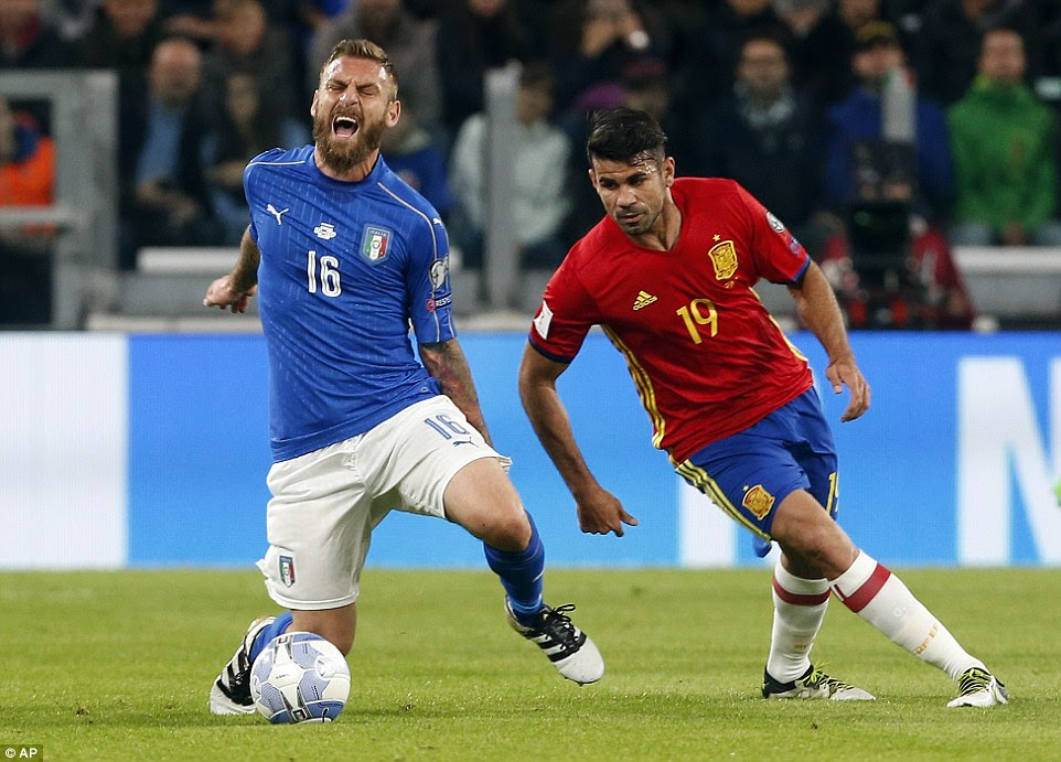 Italy midfielderDe Rossi (left) clutches the back of his leg after being caught by Diego Costa of Spain