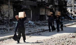 Palestinians from the besieged al-Yarmouk camp receive food aid from UNRWA, south of Damascus