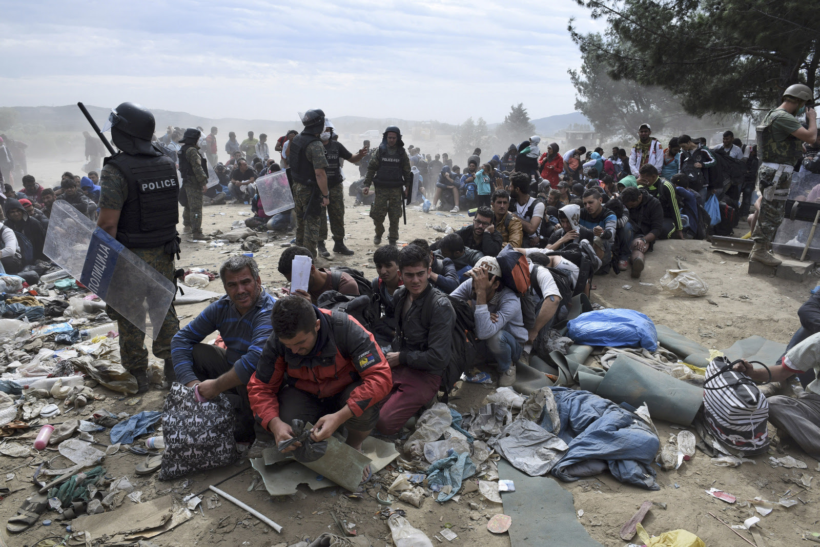 Refugees and migrants wait to cross the border from the northern Greek village of Idomeni to southern Macedonia, Monday, Sept. 7, 2015. Greece has borne the brunt of a massive refugee and migration flow of people heading into the European Union. (AP Photo/Giannis Papanikos)