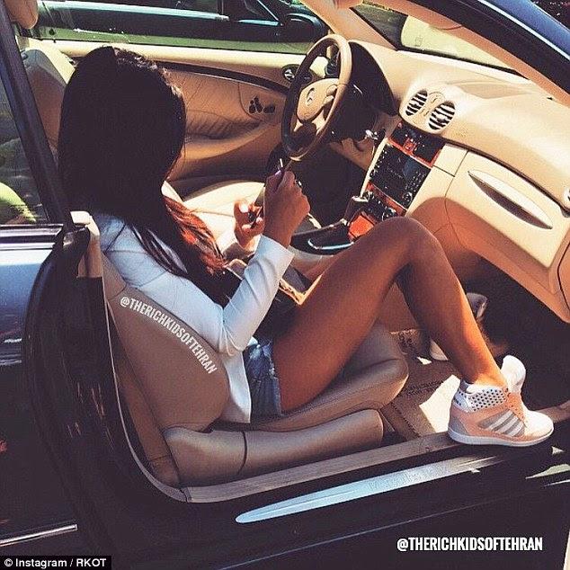 Em uma foto uma jovem mulher verifica suas mensagens enquanto relaxa em um carro esportivo de luxo