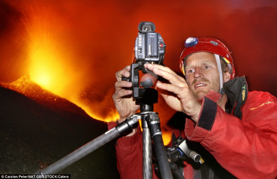 Photographer Carsten Peter adjusts his camera while Etna erupts in the background. The 53-year-old has travelled the world taking pictures of active volcanoes