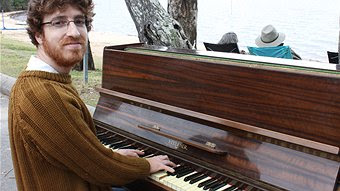 Brisbane Artist Anthony (Tenee) Dyer plays piano as part of his Floating Land installation beside La