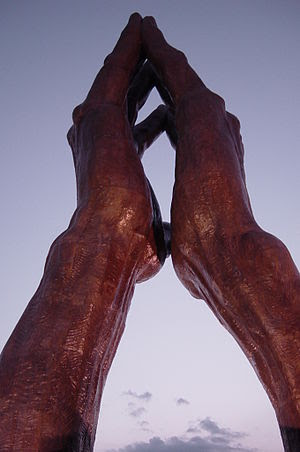 Under the ORU Praying Hands sculpture