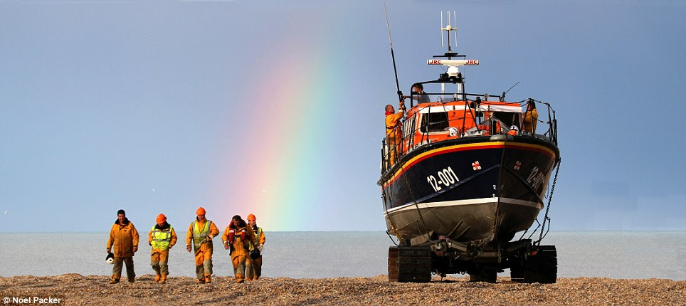 Rare sight: Noel Packer, a shore-helper, captured the calm after the storm as the crew arrived home after a rescue mission with a rainbow in the sky