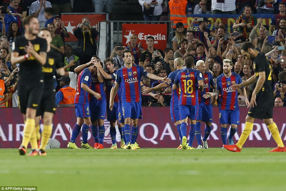 Barcelona's players surroundRakitic after he converted his cross to open the scoring against the visitors from the capital