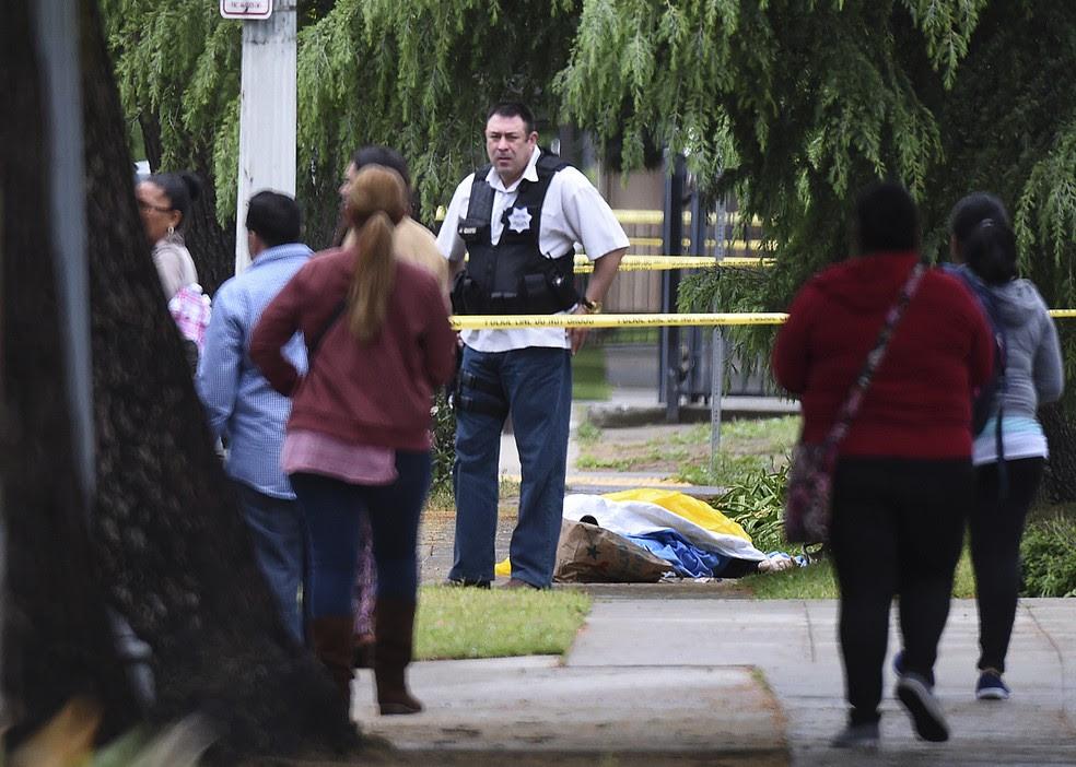 Policial isola área com corpo de vítima de atirador que fez disparos nesta terça-feira (18) em Fresno, na Califórnia (Foto: John Walker/Fresno Bee via AP)