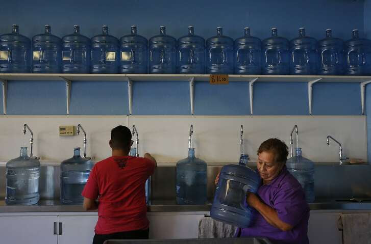 Guillermo Lopez, 31, left, and his mother Andrea Lopez, 67, fill five gallon jugs of water from Kings Pure Water August 27, 2015 in Fresno, Calif. The Lopez home ran out of water when their well ran dry in February of this year. Now Guillermo and his mother Andrea, 67, who live together, have to buy water from a store in town twice a week, each time hauling about 10 five gallon jugs between them. Andrea injured her shoulder trying to lift a jug and neither of them should be exerting themselves due to Andrea's high blood pressure and Guillermo's history of surviving Valley Fever, says Guillermo. In 2003 Guillermo nearly died of a severe case of Valley Fever that had travelled into his spine. Since then, Guillermo has been in and out of the hospital and is completely disabled. His body overheats easily and he has a weak immune system. In a home without water, he and his mother are unable to run their swamp cooler to keep the internal temperatures of the home down. In the bathroom they have a portable toilet and Guillermo found a battery-powered shower head that pumps water from their feet through a shower head, making showering easier. The whole ordeal has caused so much anxiety and stress, Guillermo said he had to go back on his anxiety pills.