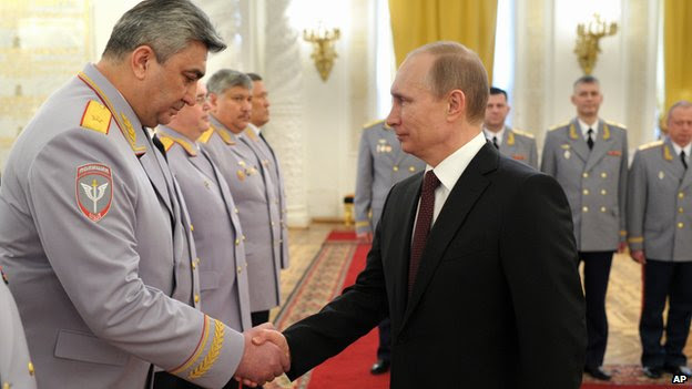 Russian President Vladimir Putin, right, shakes hands with Head of the Russian Interior Ministry's branch in the North Caucasus Kazimir Botashev at the presentation ceremony of the top military brass in the Kremlin in Moscow, Russia, Friday, March 28, 2014.