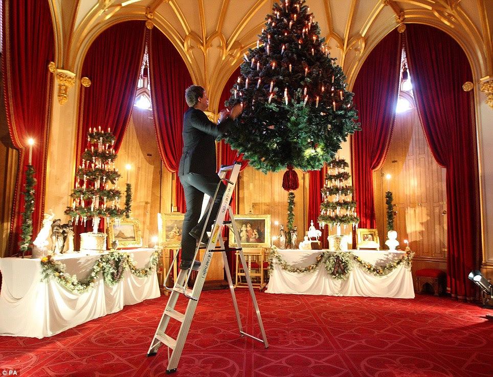 David Oakley, curador da exposição de Natal para a Coleção Real, dá os retoques finais a uma árvore de Natal que está suspenso do teto