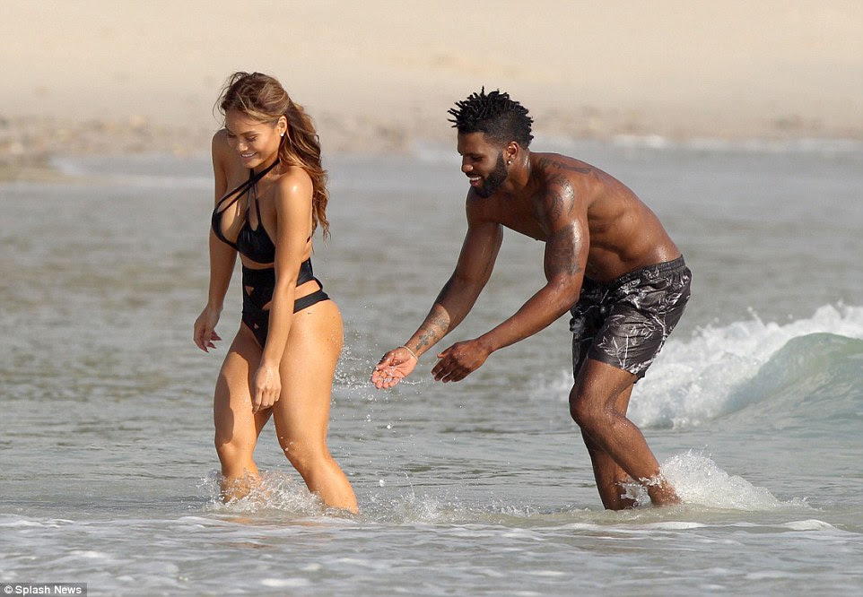 Naughty by nature: At one point the Florida native got a little silly as he splashed water on her pert bottom while she ran up the beach