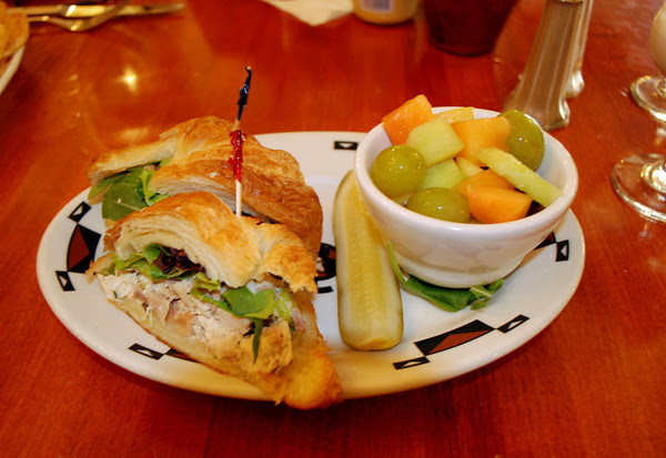 A Chicken Salad Croissant with Fresh Fruit Cup
